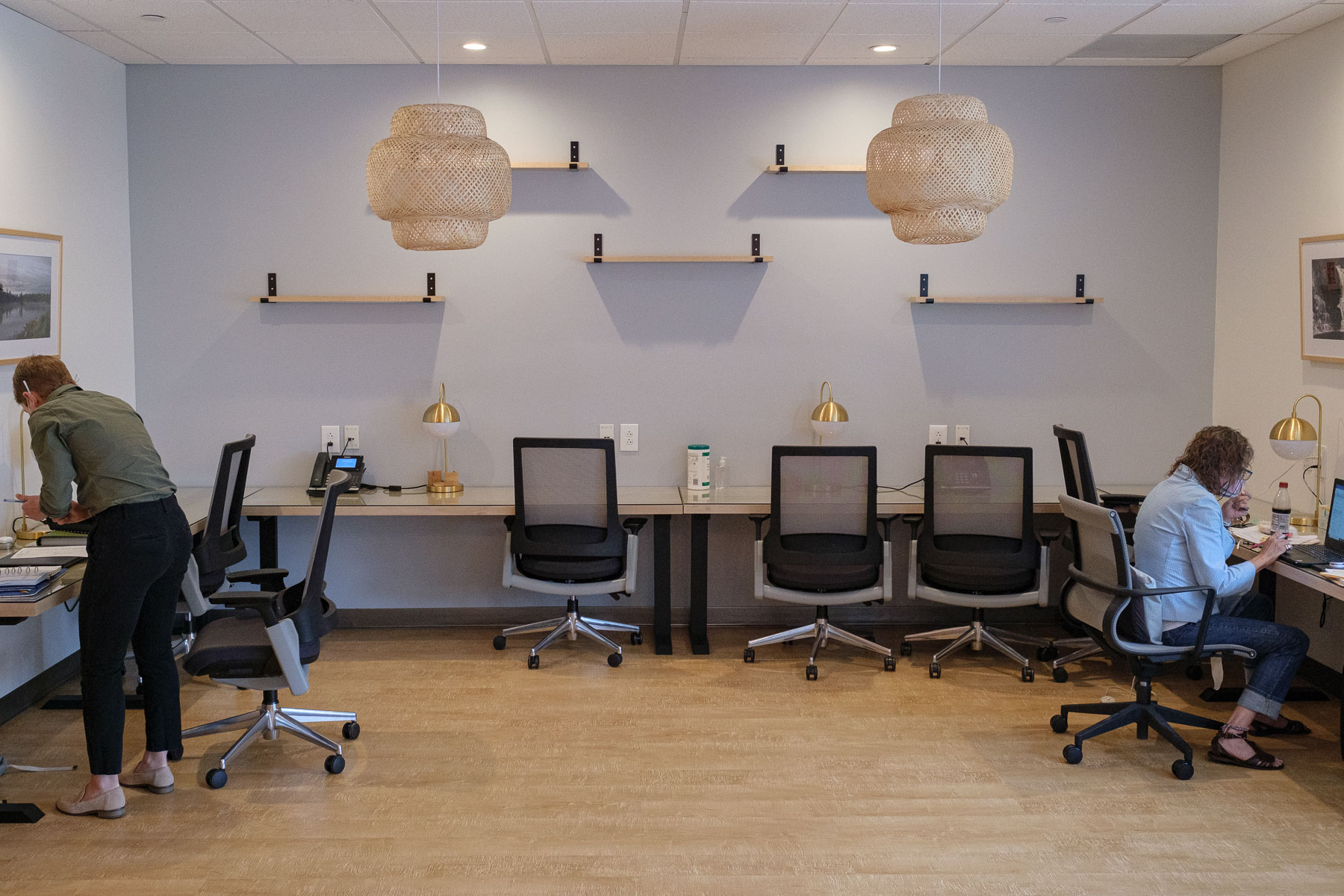 Two people work in a large room with phones, lamps, a laptop and other office materials.