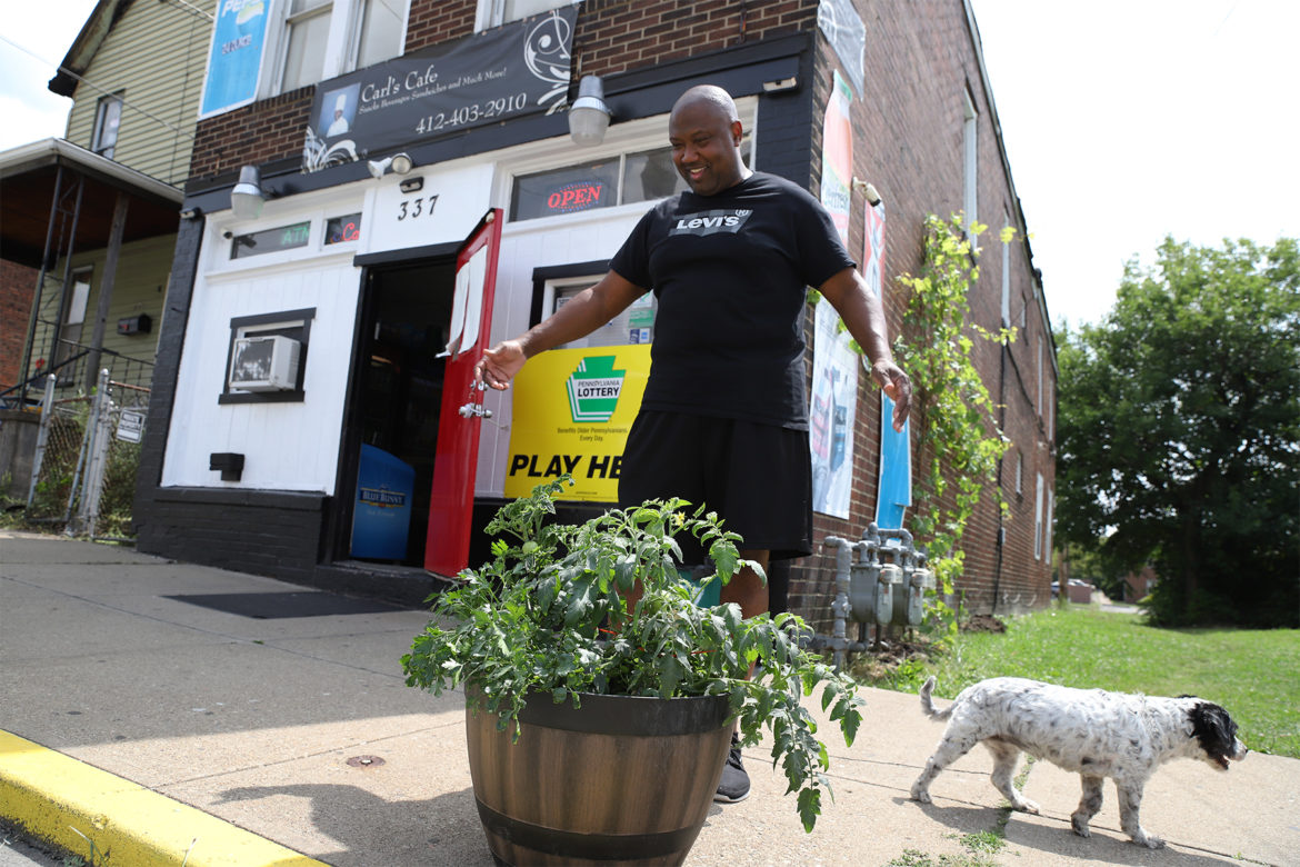 Carl Lewis stands on the sidewalk outside his store near a planter of Early Girl tomatoes. His dog Paris walks nearby. (Photo by Ryan Loew/PublicSource)