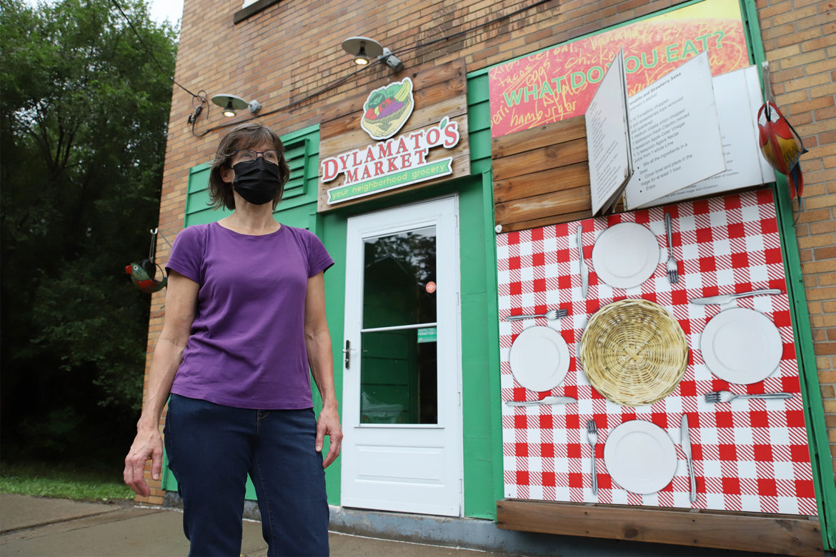 Dianne Shenk, owner of Dylamato's Market in Hazelwood, stands on the sidewalk outside her store.