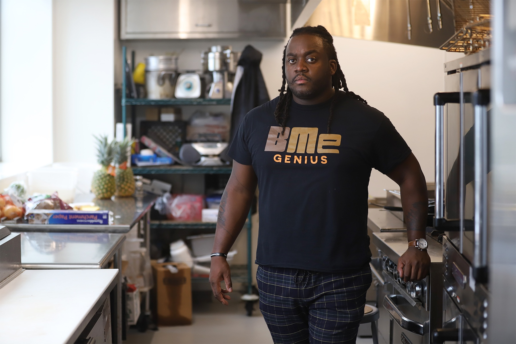 Chef Claudy Pierre stands in a kitchen area near a stove. Food and cooking items are in the background.