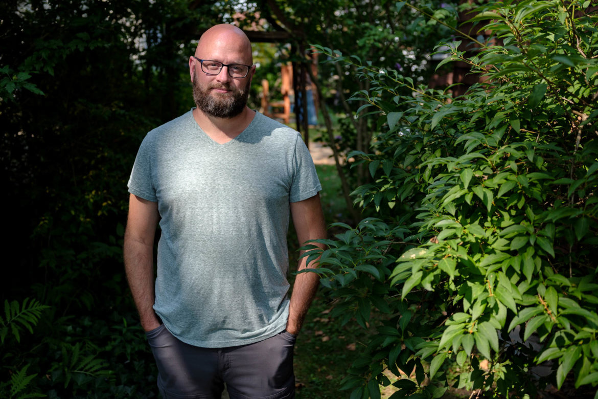 Alex Osgood stands near some greenery outside his home.