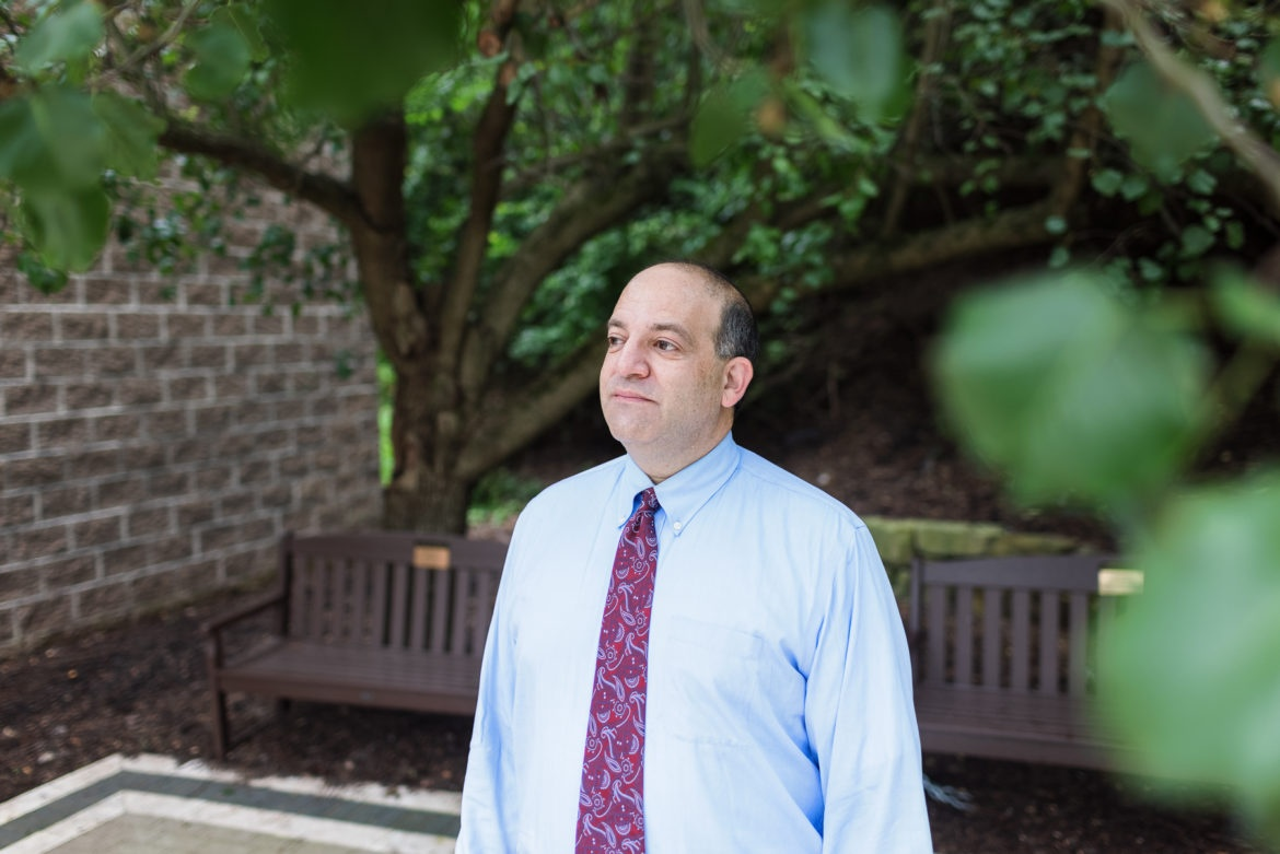 Rabbi Alex Greenbaum, wearing a dress shirt and paisley tie, stands in front of a bench outside Beth El Congregation in the South Hills.