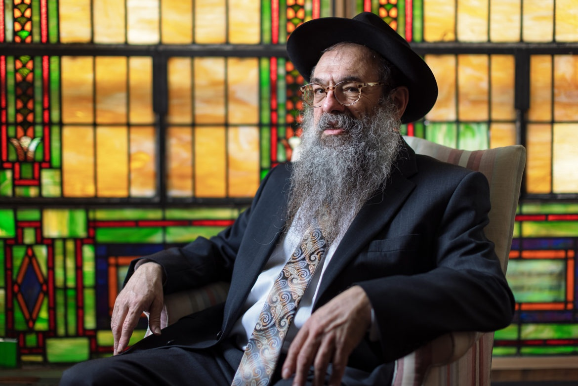 Rabbi Moishe Vogel — bearded, with glasses and a hat — sits before a stained glass window at the Aleph Institute in Squirrel Hill.