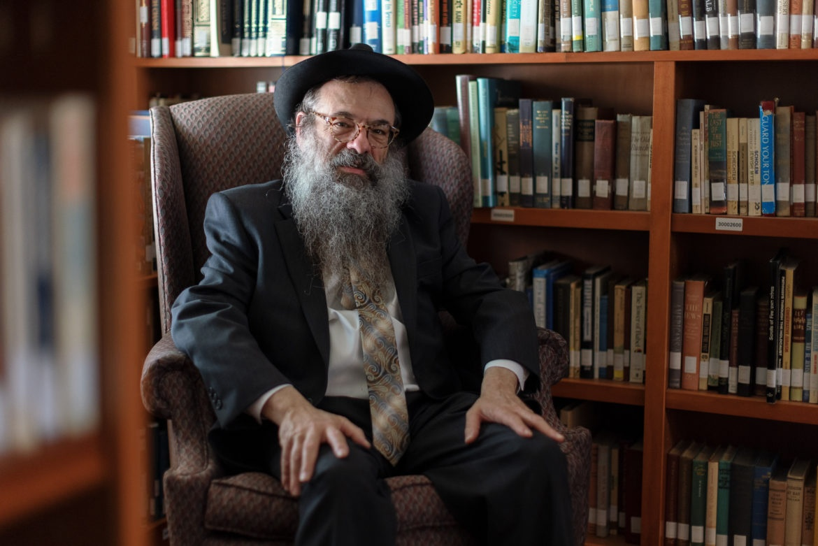Rabbi Moishe Vogel of the Aleph Institute sits in an armchair, surrounded by bookshelves.