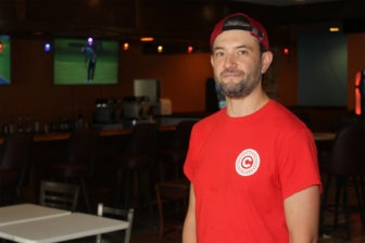 Jeffrey Katrencik stands inside a room with tables and a bar facing the camera.