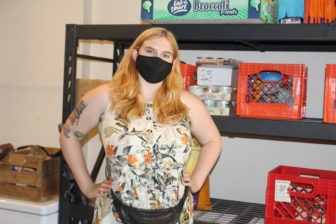 Kacy McGill stands in a room in front of a shelves of food.