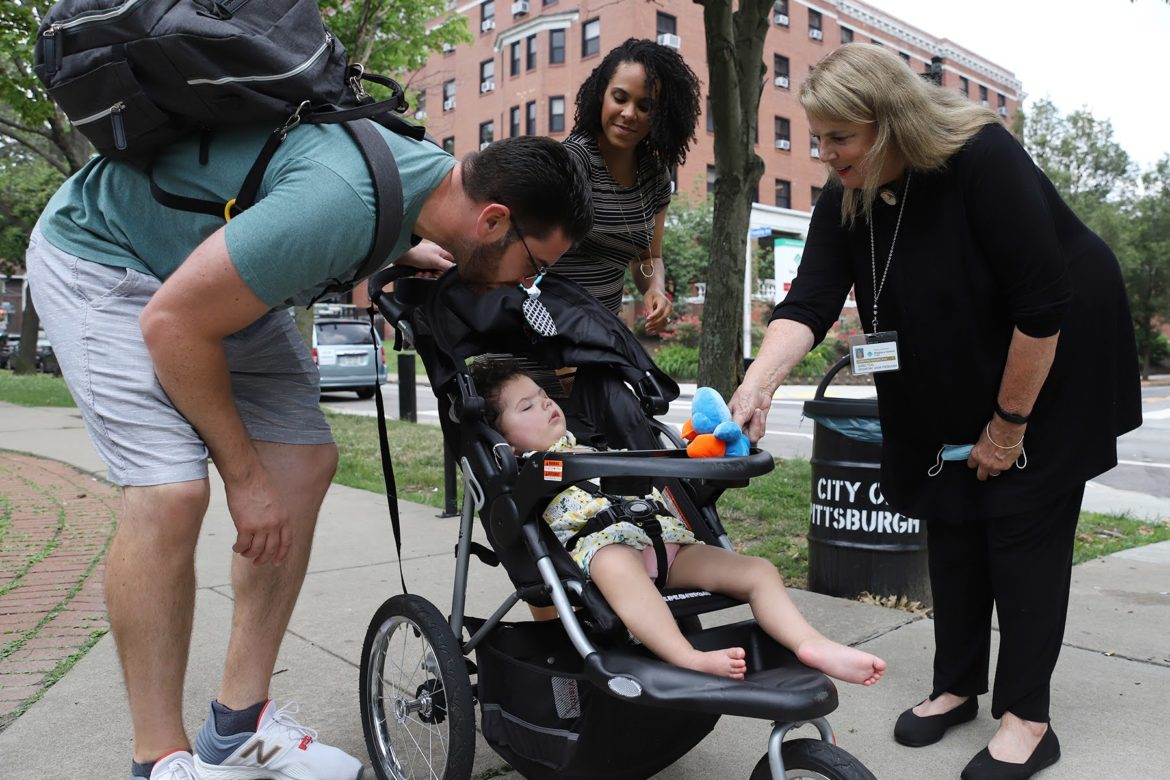 Todd and Kelsey Johnson, along with their 22-month-old daughter, visit with Christine Roman-Lantzy in Friendship Park in July