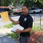 Allentown Housing Inspector Modesto Medina shows an example of the certificate property owners receive when their building passes inspection. At this location in the city's southern neighborhoods, Medina noted a discarded car wheel and other debris amid high weeds and grass, but the owner did not show up for the scheduled inspection. (Photo by Rich Lord/PublicSource)