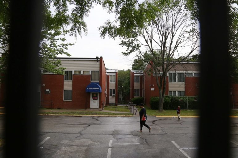 A resident of Hi View Gardens and her young son, seen through a gate, cross the main parking lot of the five-building McKeesport complex. The Allegheny County Health Department found 347 housing health code violations at Hi View and nearby Midtown Plaza from 2017 through 2020, and it collected $2,500 in penalties. (Photo by Ryan Loew/PublicSource)
