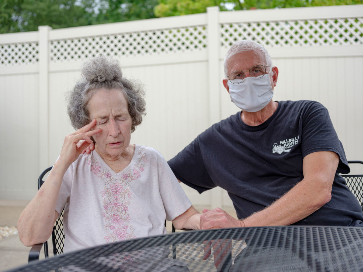 Two people sitting a black metal table, one embraces the other and is wearing a white face mask