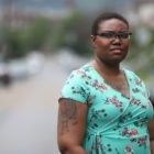 Tanisha Bowman, wearing a blue floral dress and glasses, stands outside posing for a photo.