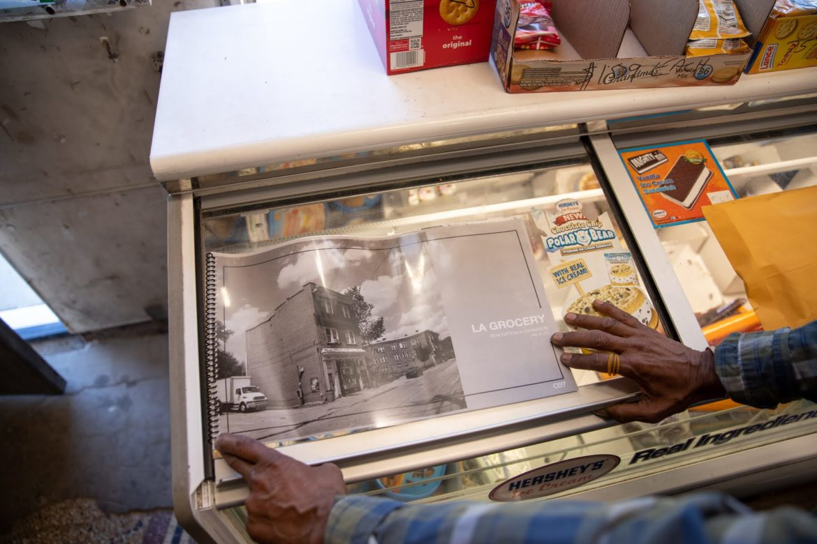 """Wilbert """"Bim"""" Moore, one of the brothers who operate LA Grocery on Larimer Avenue, shows plans for the expansion of the 30-year-old store. (Photo by Kaycee Orwig/PublicSource)"""