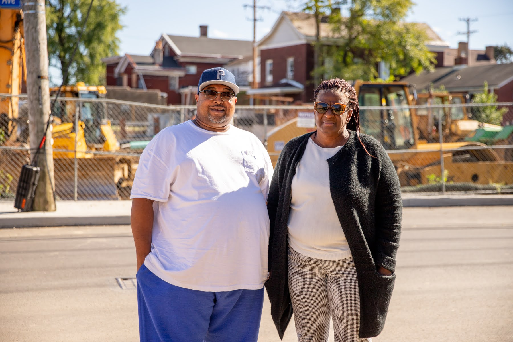 Malik Morris (left), the community engagement manager of the Larimer Consensus Group, and Donna Jackson, the group's board chair, stand on Larimer Avenue in front of the site of ongoing housing construction funded by a federal Choice Neighborhoods grant. (Photo by Kaycee Orwig/PublicSource)