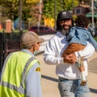 Dontae Comans walks and carries his daughter on a sunny day in Wilkinsburg